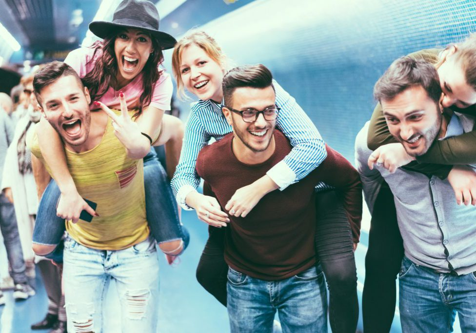 Group of friends having fun in underground metropolitan station - Young people hanging out ready for party night - Friendship and youth lifestyle concept - Focus on center girl face
