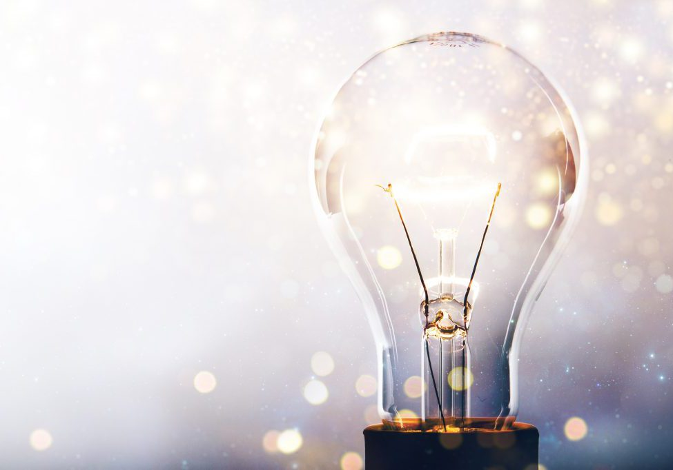 Glowing glass light bulb on background